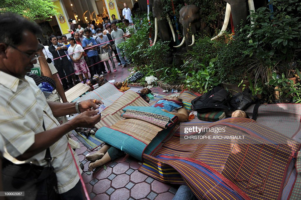 A man watches the identity card of a dead anti-government protester killed in a gunbattle the day before at a temple which had been turned into a shelter within an anti-government protest site in downtown Bangkok on May 20, 2010. Gunshots rang out near a Buddhist temple in the heart of an anti-government protest zone in Bangkok, and soldiers were advancing on foot along an elevated train track, an AFP photographer saw. Thai security forces stormed the 'Red Shirts' protest camp on May 19 in a bloody assault that forced the surrender of the movement's leaders who asked their supporters to disperse. AFP PHOTO/Christophe ARCHAMBAULT