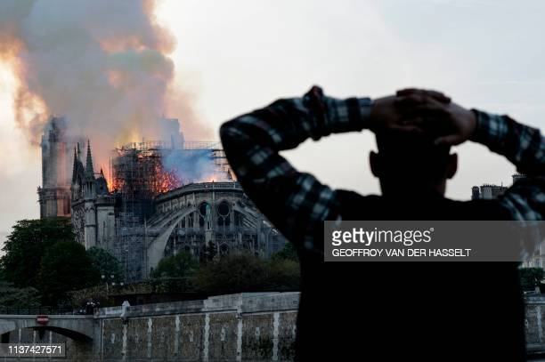 TOPSHOT A man watches the landmark NotreDame Cathedral burn engulfed in flames in central Paris on April 15 2019 A huge fire swept through the roof...