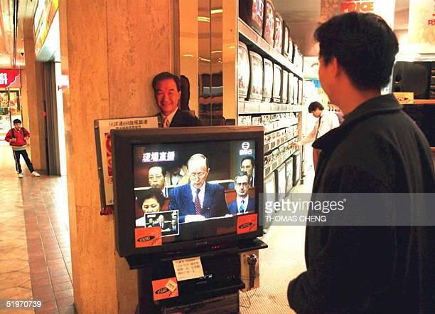 A man watches the live telecast of Hong Kong Financial Secretary Sir Hamish Macleod delivering his budget proposal 01 March in Hong Kong Macleod...