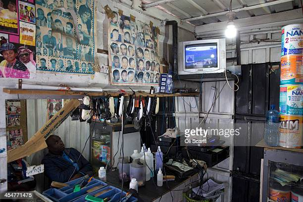 A man watches the official memorial service for Nelson Mandela on a television inside a barbers shop in Alexandra Township on December 10 2013 in...