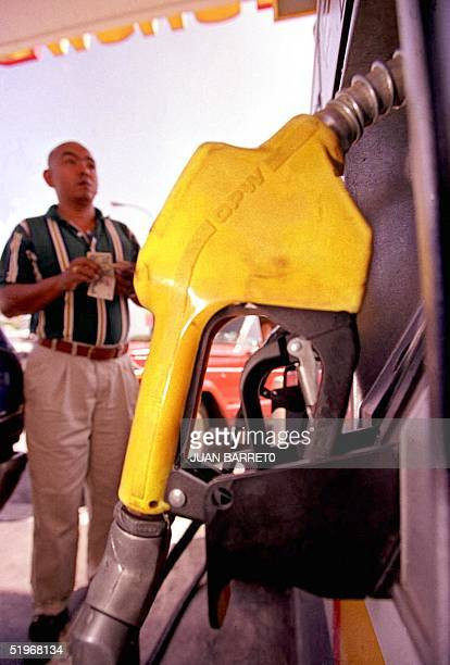 A man watches the price to pay at a gasoline station in Caracas Venezuela 07 September 2000 Oil prices reached a tenyear high 06 September when it...