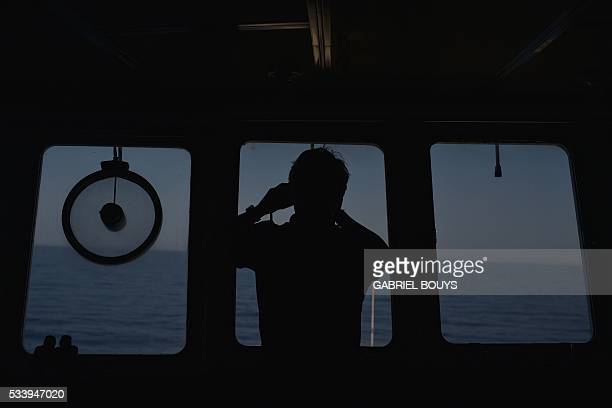A man watches the sea with binoculars during a rescue operation of migrants and refugees of the 'Aquarius' a former North Atlantic fisheries...