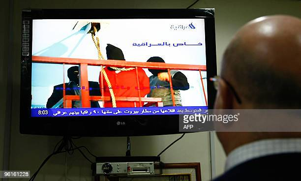 A man watches the state run AlIraqiya television channel showing the execution of Ali Hassan alMajid known as 'Chemical Ali' in Baghdad on January 25...