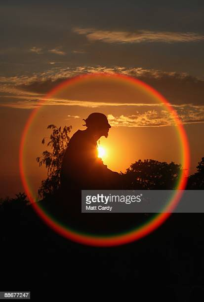 Man watches the sunset at the stone circle as music fans start to arrive at the Glastonbury Festival site at Worthy Farm, Pilton on June 24, 2009 in...