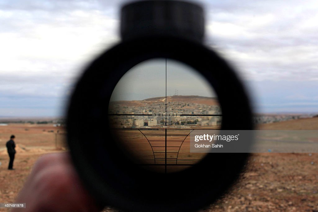 A man watches the Syrian town of Kobani through a sniper rifle binocular from near the Mursitpinar border crossing, on the Turkish-Syrian border in the southeastern town of Suruc, October 19, 2014 in Sanliurfa, Turkey. Kurdish fighters in Syrian city of Kobani have pushed back Islamic State militants in a number of locations as U.S. air strikes on ISIS positions continue in and around the city. In the past month more than 200,000 people from Kobani have fled into Turkey.