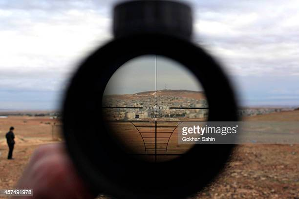 A man watches the Syrian town of Kobani through a sniper rifle binocular from near the Mursitpinar border crossing on the TurkishSyrian border in the...
