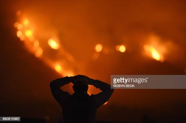 TOPSHOT A man watches the Thomas Fire in the hills above Carpinteria California December 11 2017 The Thomas Fire in California's Ventura and Santa...