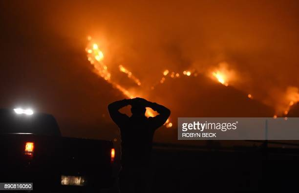 A man watches the Thomas Fire in the hills above Carpinteria California December 11 2017 The Thomas Fire in California's Ventura and Santa Barbara...
