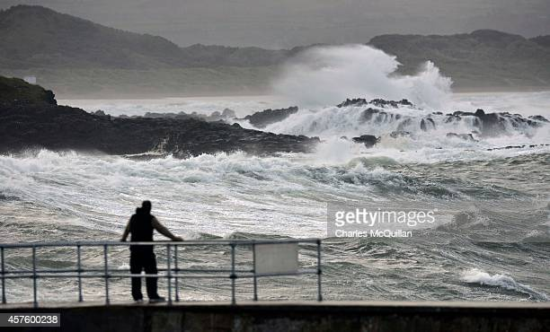 A man watches the turbulent sea from the harbour wall at Portstewart on October 21 2014 in County Antrim Northern Ireland The Met Office has issued a...