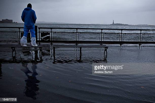 A man watches the waves in New York Harbor from Battery Park during the arrival of Hurricane Sandy on October 29 2012 in New York City The core of...