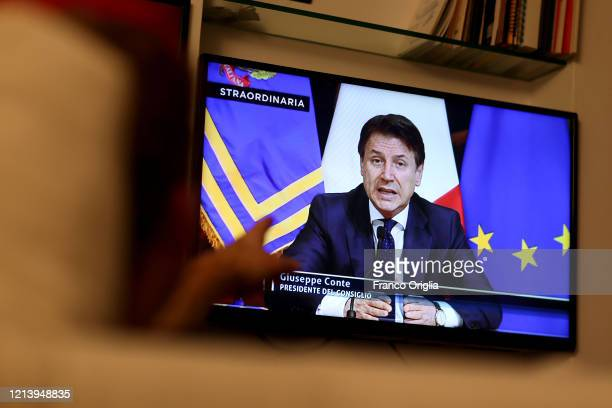 A man watches tv as Italian Prime Minister Giuseppe Conte announces the shut down of all nonessential production activities during a special Facebook...