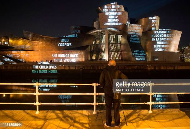 A man watches US artist Jenny Holzer's projection mapping creation entitled 'For Bilbao' and projected on the Guggenheim Bilbao Museum's facade as...