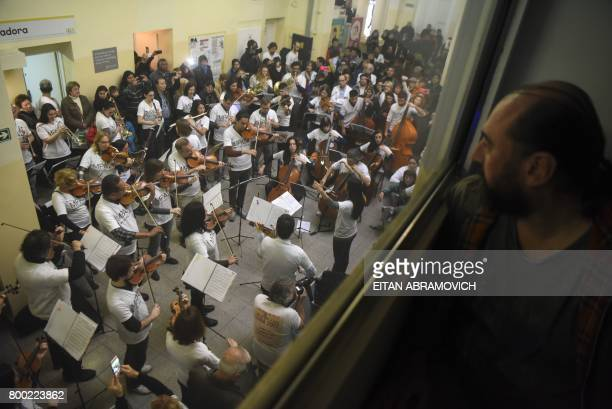 A man watches volunteer members of Musica Para el Alma giving a flash mob concert in the main hall of the Alvarez Hospital in Buenos Aires on June 12...