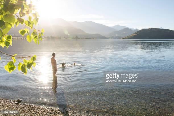 Man watches woman float in mountain lake, sunrise