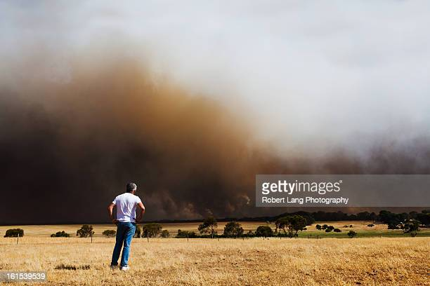 man watching a bush fire burn - australian bushfire stock pictures, royalty-free photos & images