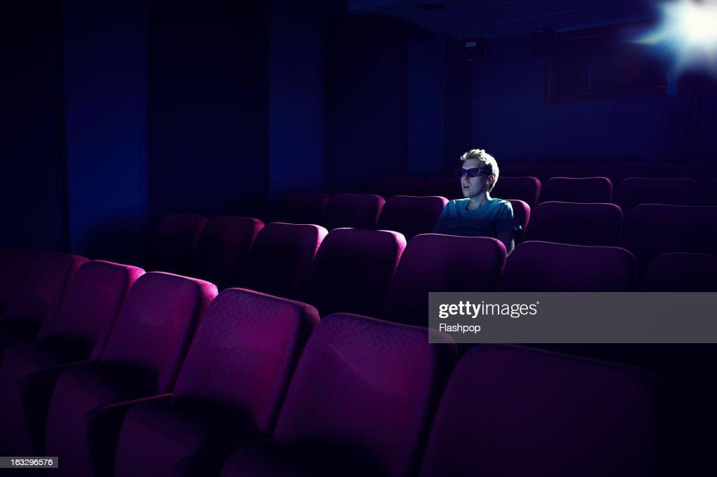 Man watching a movie in empty cinema : Stock Photo