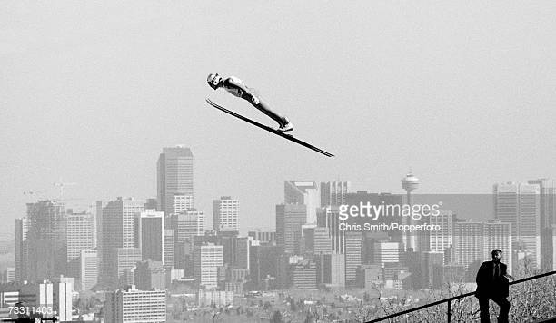 A man watching a ski jump competitor against the Calgary skyline during the 1988 WInter Olympics
