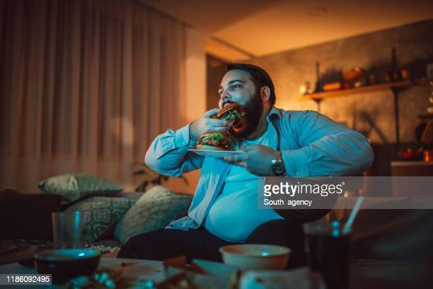 man watching a sports match and eating burger - solo 2018 film stock pictures, royalty-free photos & images