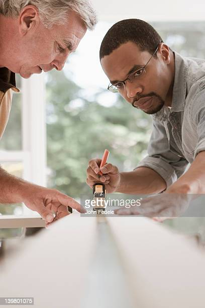 Man watching carpenter measuring lumber