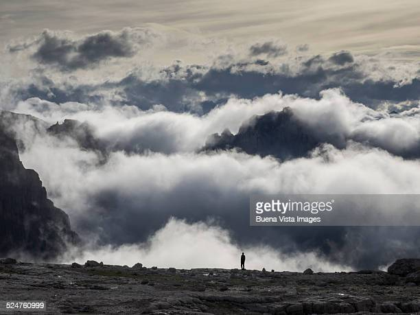 Man watching clouds and mountains in late afternoo