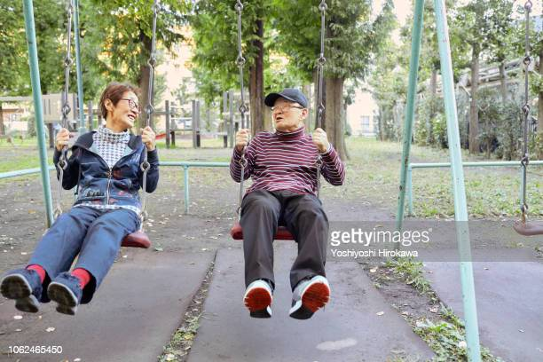 man watching far away on swing with his wife - snapping the ball stock pictures, royalty-free photos & images