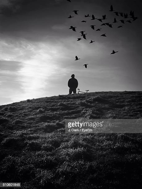 Man watching flying birds