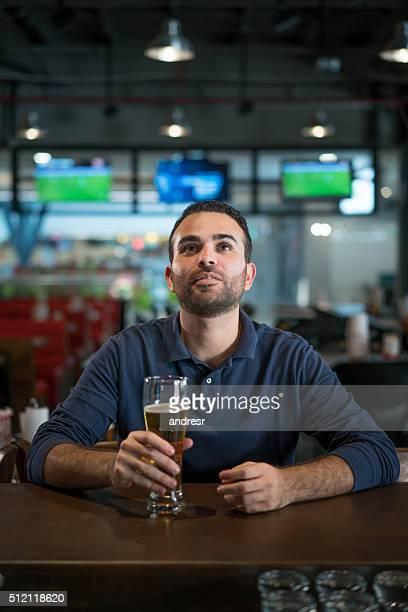 Man watching football at the bar
