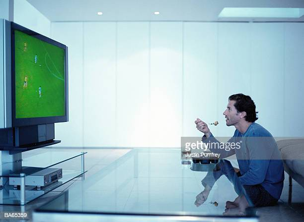man watching football on television, eating tv dinner - man cave stock pictures, royalty-free photos & images