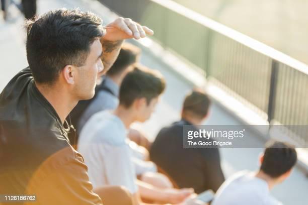 man watching game from stadium bleachers - voetbalcompetitie sportevenement stockfoto's en -beelden
