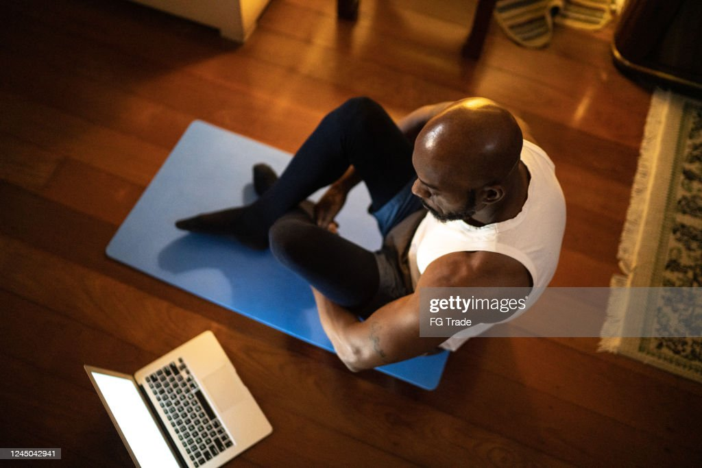 Man watching gym class on laptop and doing exercises at home : Stock Photo