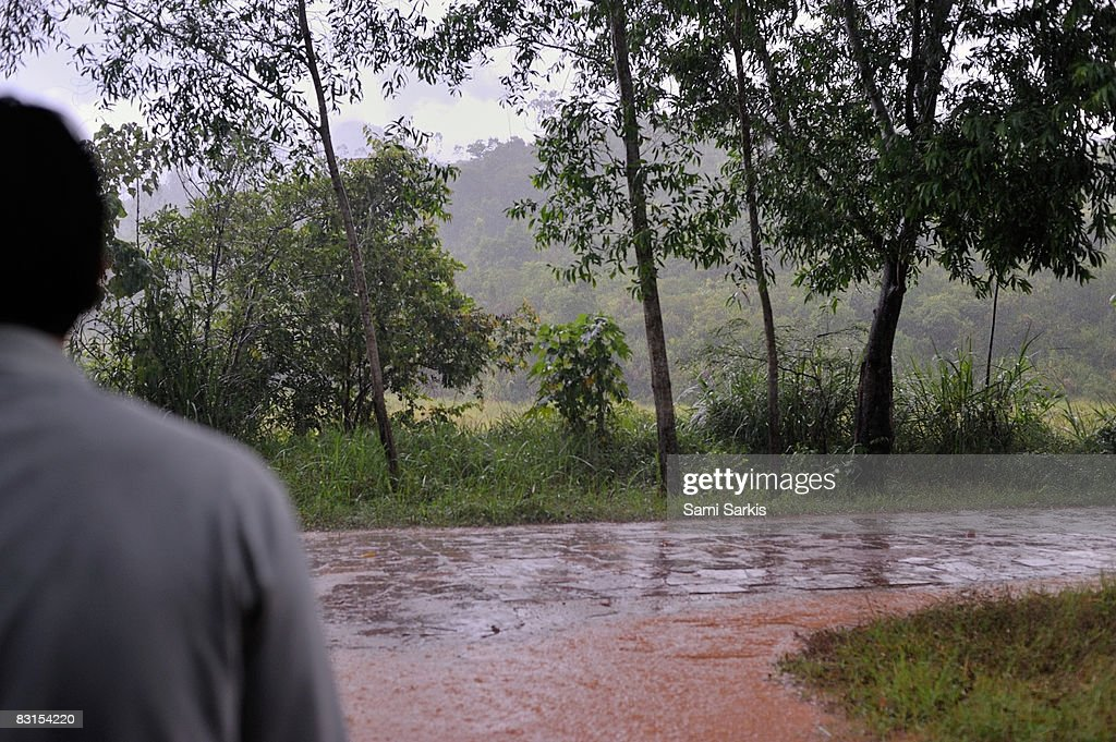 Man watching heavy rain on country road : Stock Photo