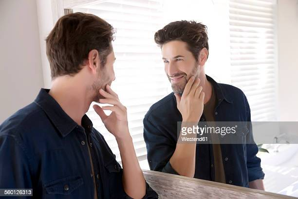 Man watching himself at bathroom mirror
