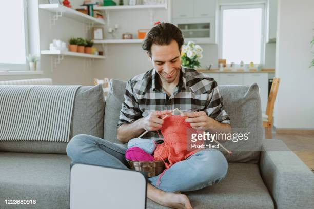 man watching knitting tutorial with needles - knitting stock pictures, royalty-free photos & images