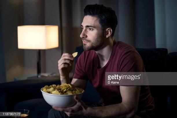 自宅で映画を見ている男 - ポテトチップス ストックフォトと画像