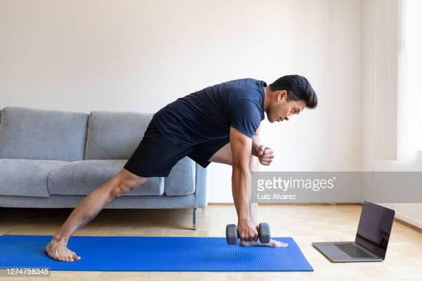 man watching online video and doing dumbbell exercises at home - men exercising stock pictures, royalty-free photos & images