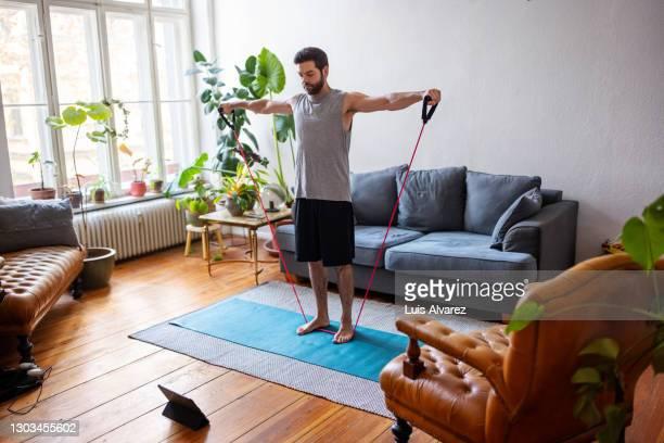 man watching online videos and doing exercise at home - un seul homme d'âge moyen photos et images de collection