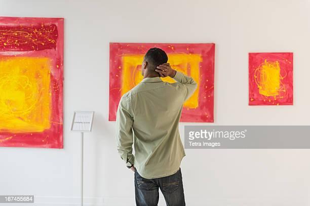 Man watching paintings in modern art gallery