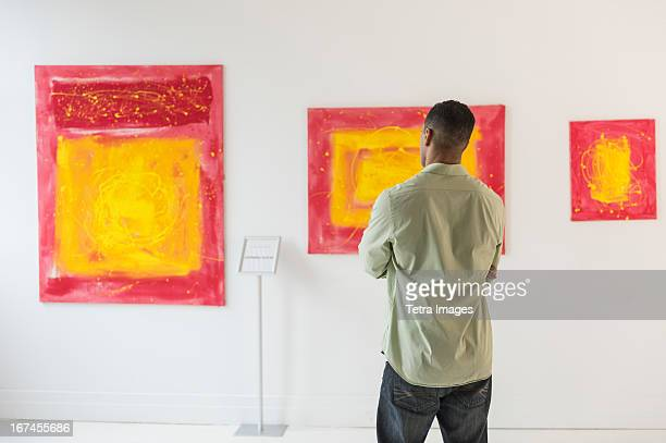 man watching paintings in modern art gallery - modern art stock pictures, royalty-free photos & images