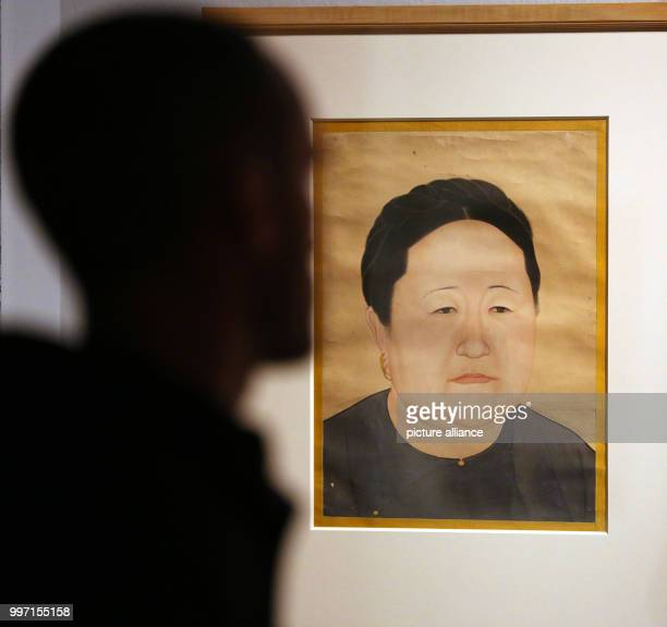 A man watching portrait paintings from China depicting Empress dowager Xiaozhuangwen in the Kulturforum at the Matthaikirchplatz in Berlin Germany 10...