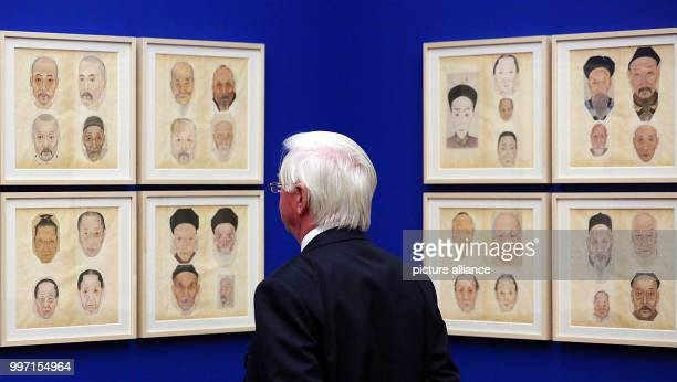 A man watching portrait paintings from China in the Kulturforum at the Matthaikirchplatz in Berlin Germany 10 October 2017 The exhibition 'Faces of...