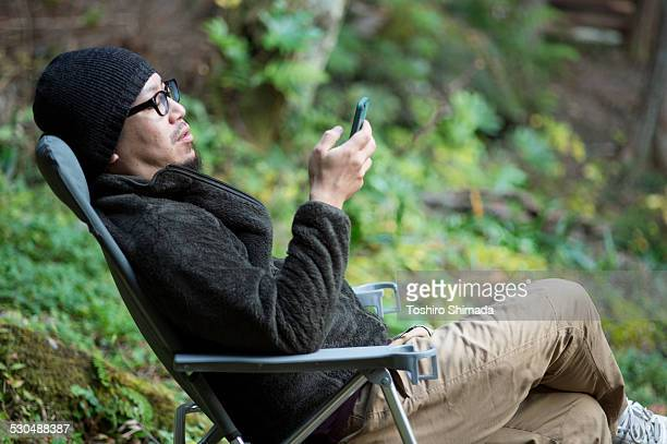 A man watching smartphone in the forest