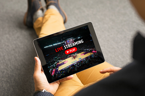 Man watching sports on live streaming online service 938423322