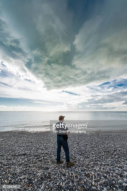Man watching storm clouds gathering over the sea
