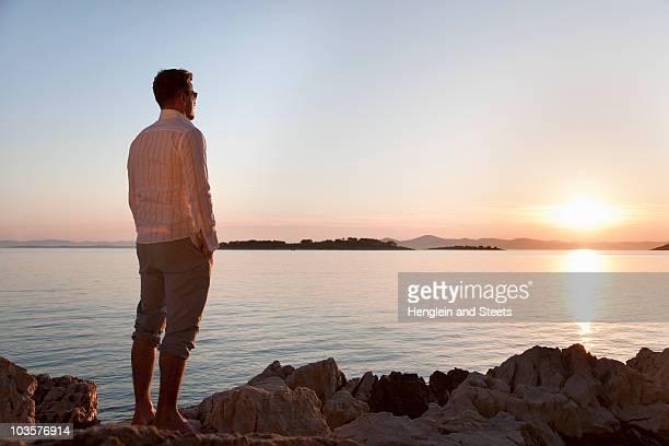 man watching sun set at rocky beach - handen in de zakken stockfoto's en -beelden