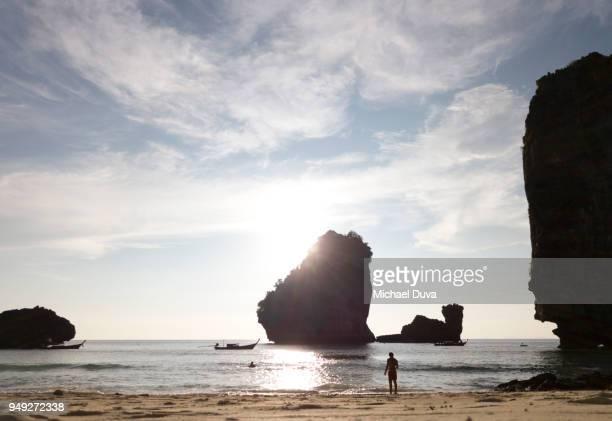 Man watching sun set on rocky beautiful beach