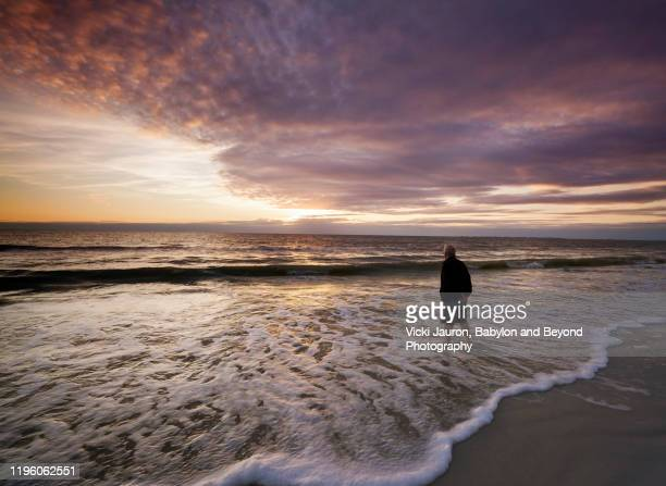 man watching sunset at fort myers beach, florida - fort myers beach stock pictures, royalty-free photos & images