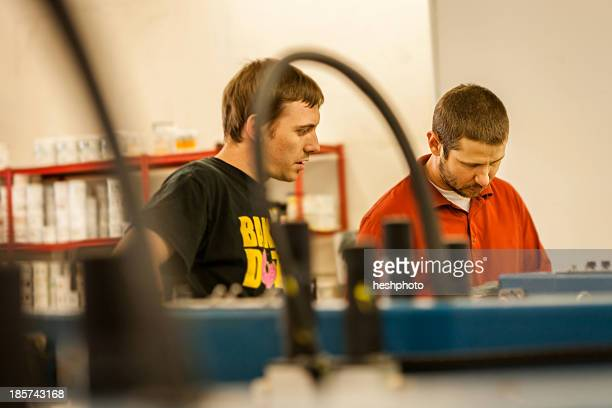man watching supervisor in screen print workshop - heshphoto stock pictures, royalty-free photos & images