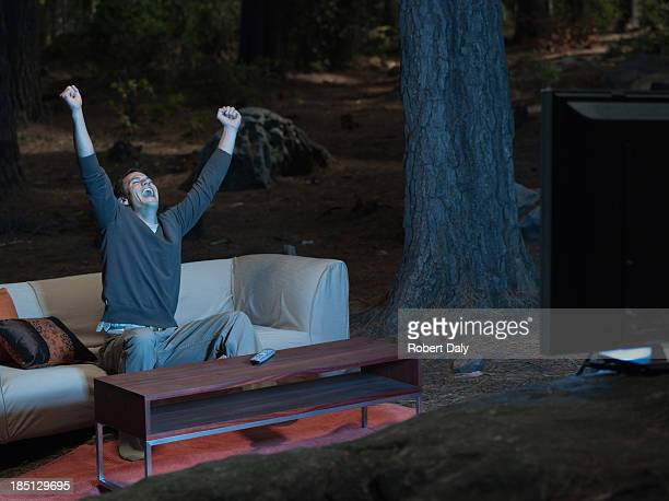 A man watching television and laughing outdoors in the woods