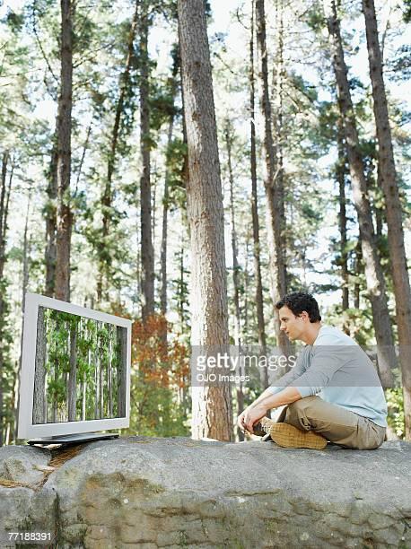 Ein Mann vor dem Fernseher im Freien im Wald