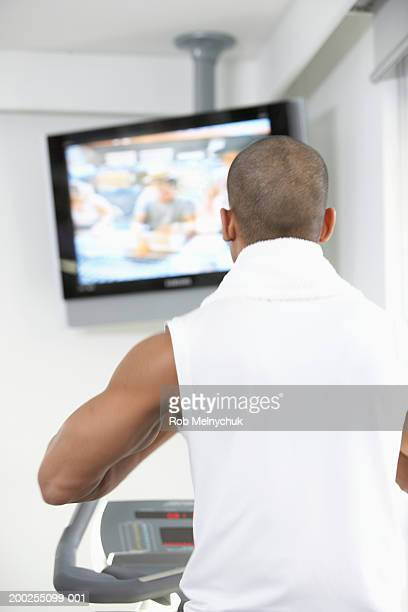 man watching television while using exercise machine, rear view - tela grande - fotografias e filmes do acervo